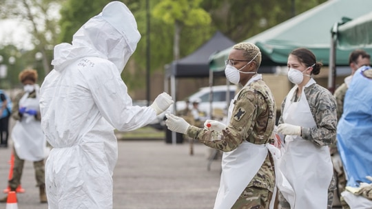 Louisiana National Guard Soldiers and Airmen wearing protective gear collect nasal swabs from patients during a drive-through community based COVID-19 testing site located at Louis Armstrong Park, New Orleans, La., March 20, 2020. Governor John Bel Edwards has activated over 300 Louisiana Guardsmen so far to assist with the COVID-19 response. (U.S. Air National Guard photo by Senior Master Sgt. Dan Farrell)