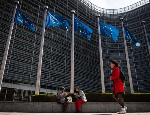 A man and woman have their lunch as they sit beneath the EU flags near the EU Council headquarters on April 10, 2019, in Brussels, Belgium. According to a new report, the bloc has been spending more on defense in general, but not on equipment and new technology. (Photo by Leon Neal/Getty Images)