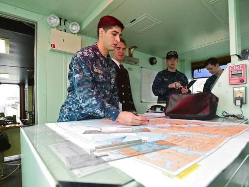 In this Feb. 22, 2018, photo, Midshipman Alejandro Carriazo, left, looks at a navigational chart aboard YP705. Midshipmen learn seamanship skills aboard Yard Patrol boats at the Naval Academy (Paul W. Gillespie/The Baltimore Sun via AP)