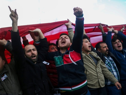 People shout slogans in support of Turkish soldiers during the funeral of Ali Akdogan in Izmir, Turkey, Sunday, Feb. 11, 2018. Akdogan was one of 12 Turkish soldiers killed Saturday during Turkey's Operation Olive Branch against the Syrian Kurdish militia that started on Jan. 20 with Ankara's cross-border incursion into the enclave of Afrin, Syria. (Emre Tazegul/AP)