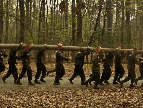 Male and female Officer Candidate School candidates struggle as they run through the woods during The Montford Point Challenge in 2012. (Lance Cpl. Emmanuel Ramos/Marine Corps)
