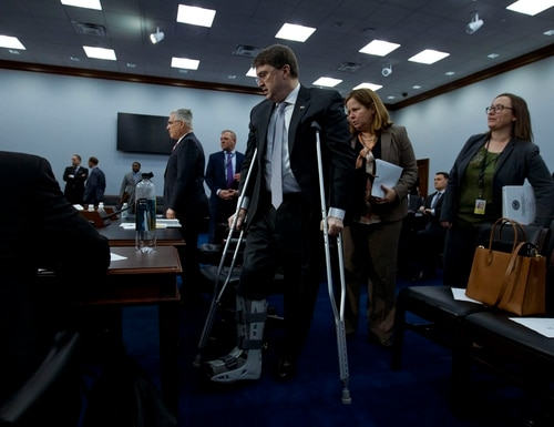 Veterans Affairs Secretary Robert Wilkie walks with crutches into a crowded meeting room at the start of a House Appropriations Committee hearing on Capitol Hill on Feb. 26, 2019. This year's annual budget hearing with the secretary, set for Thursday morning, will look very different because of coronavirus restrictions on the Capitol campus. (Jose Luis Magana/AP)