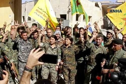 Fighters from the U.S.-backed Syrian Democratic Forces celebrate their victory Tuesday in Raqqa, Syria. (Hawar News Agency via AP)