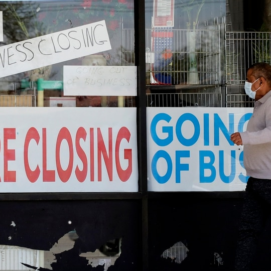 A man looks at signs displayed of a store closing due to the coronavirus pandemic in Niles, Ill., on May 21, 2020. (Nam Y. Huh/AP)