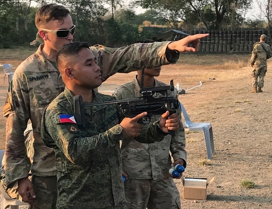A U.S. soldier with 5th Battalion, 20th Infantry Regiment, teaches an Armed Forces of the Philippines soldier how to operate the M320 Grenade Launcher Module March 11, 2019, at Nueva Ecija Province, Philippines. (U.S. Army)