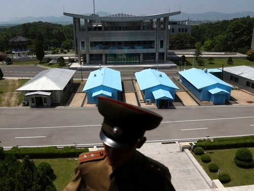 A South Korean building complex is seen in the background as North Korean soldiers guard the truce village at the Demilitarized Zone (DMZ) which separates the two Koreas in Panmunjom, North Korea, Wednesday, June 20, 2018. A tour guide Hwang Myong Jin, on the northern side of the Demilitarized Zone that divides the two Koreas, says that since the summits between North Korean leader Kim Jong Un and the presidents of South Korea and the United States, things have quieted down noticeably in perhaps the most iconic symbol of the one last place on Earth where the Cold War still burns hot. (Dita Alangkara/AP)