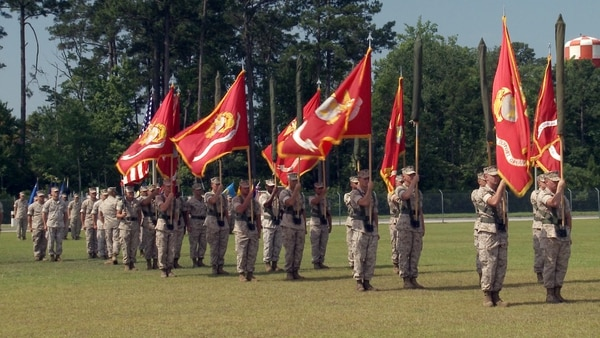 """MARSOC Marines roll up their colors before unfurling new ones that mention the historic """"Raiders"""" name that was approved for the unit at a ceremony Friday , June 19, 2015."""