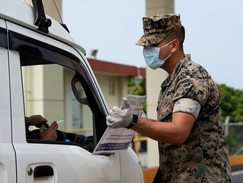Marines conduct health and wellness checks of pool individuals entering Camp Foster in an effort to combat the spread of COVID-19, on Camp Foster, Okinawa, April 3, 2020. (Cpl. Kameron Herndon/Marine Corps)
