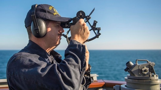 Quartermaster 1st Class Christopher Holgate uses a sextant on the bridge wing aboard the forward-deployed guided-missile destroyer Carney while operating in the Black Sea. As an E-6 quartermaster, Holgate could net up to $600 a month in Sea Duty Incentive Pay for extending at least a year. (photo by MC2 James R. Turner/Navy)