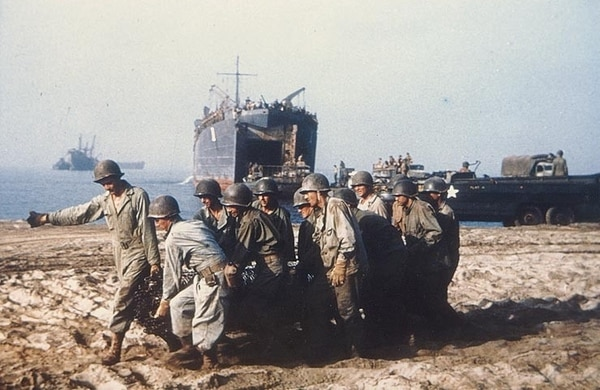 U.S. Army Engineers haul a roll of wire mesh into position to make a beach roadway, at Salerno, circa September 1943. LST-1 is in the center background. (National Archives)