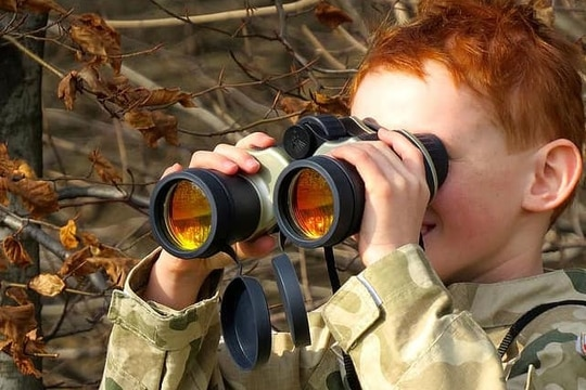 A small child dressed in a military uniform looks through binoculars. (Royalty free/Pikst)
