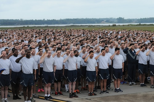 Airmen render a salute during the National Anthem prior to the start of a 5K run on the flight line in 2014. (Kemberly Groue/Air Force)