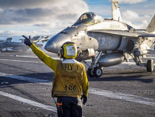 "A sailor directs the pilot of an F/A-18C Hornet from the ""Blue Blasters"" of Strike Fighter Squadron 34 on the flight deck of the carrier Carl Vinson. The Legacy Hornet completed its sundown cruise when the Vinson returned to San Diego. (MC2 Sean M. Castellano/Navy)"