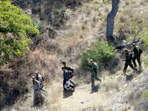 U.S. Border Patrol agents escort four undocumented immigrants captured near the U.S.-Mexico border on April 23, 2015. (Staff Sgt. Scott Tynes/Mississippi Army National Guard)