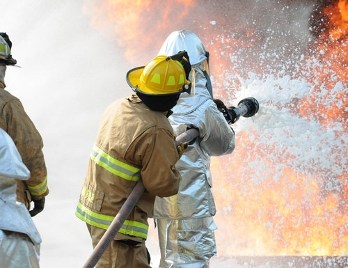 U.S. Air Force and New Jersey state fire protection specialists from the New Jersey Air National Guard's 177th Fighter Wing battle a simulated aircraft fire with Aqueous Film Forming Foam at Military Sealift Command Training Center East in Freehold, N.J., on June 12, 2015. (Airman 1st Class Amber Powell/Air National Guard)