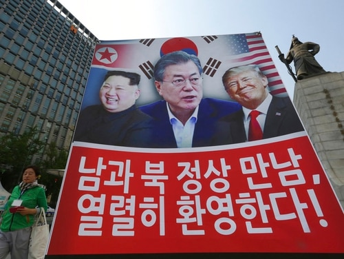 A banner showing U.S. President Donald Trump, right, South Korean President Moon Jae-in and North Korean leader Kim Jong Un, left, is displayed to support the summit between two Koreas in Seoul, South Korea, Friday, April 27, 2018. The sign reads