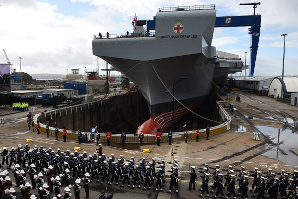 Royal Navy servicemen march past HMS Prince of Wales before a naming ceremony for the aircraft carrier at Rosyth Dockyard in September 2017 in Rosyth, Scotland. Completion of the ship raises questions about what's next for the British shipbuilding industry. (Jeff J. Mitchell/Getty Images)