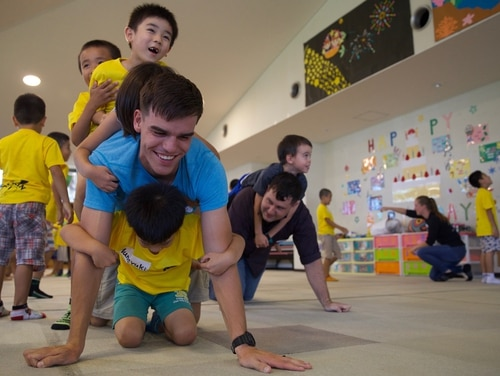 Children hitch a ride on Lance Cpl. Samual Buhr, left, and Lance Cpl. Kristopher Coalson, right, at Kin District Daycare in Okinawa, Japan, on Aug. 14, 2018, during a military volunteer program. (Lance Cpl. Harrison Rakhshani/Marine Corps)
