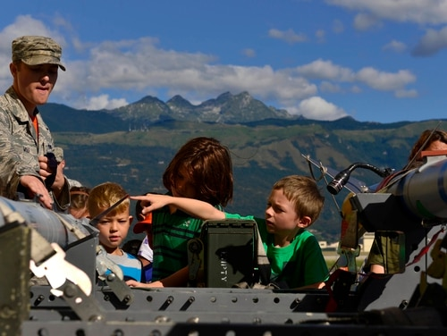 A member of the 31st Munitions Squadron talks with children about working with missiles during a family day at Aviano Air Base in Italy in June 2015. Military officials are reviewing rules regarding families living at overseas bases for ways to ease restriction on employment for military spouses. (Airman 1st Class Cary Smith/Air Force)