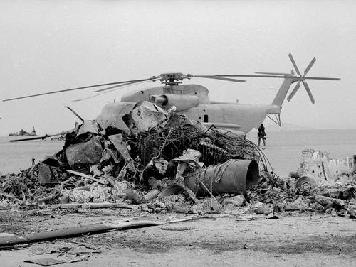 FILE - In this April 26, 1980 file photo, an undamaged helicopter sits on the ground behind the charred remains of a second U.S. helicopter in the Iranian desert of Dasht-E-Kavir, April 26, 1980. The site, about 300 air miles from Tehran, was where the United States rescue effort for those held hostage in Tehran was abandoned, and where a U.S. helicopter and transport aircraft collided. Nov. 4, 2019, will mark the 40th anniversary of the start of the 444-day hostage crisis that soured relations between the U.S. and the Islamic Republic for decades to come. (AP Photo, File)