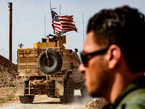 A U.S. soldier sits atop an armored vehicle during a demonstration by Syrian Kurds against Turkish threats next to a base for the US-led international coalition on the outskirts of Ras al-Ain town in Syria's Hasakeh province near the Turkish border on Oct. 6, 2019. (Delil Souleiman/via Getty Images)
