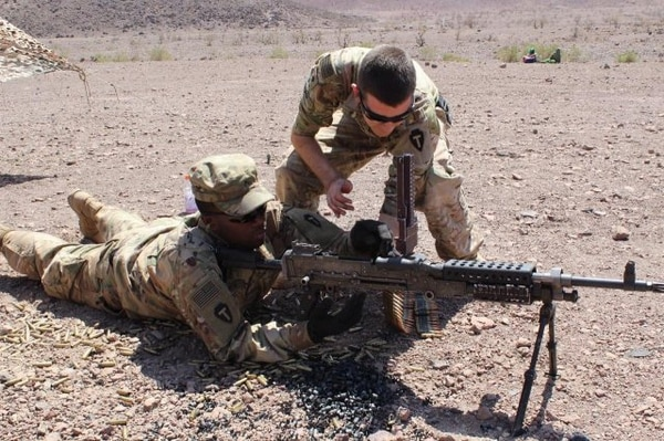 Spc. Matt Oldham assists a fellow member of the infantry in weapons training during a deployment to Djibouti. (Army)
