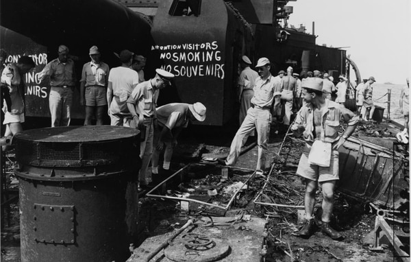 The cruiser Pensacola's afterdeck, looking forward, showing damage inflicted during the Operation Crossroads atomic bomb tests at Bikini, in July of 1946. Men in the foreground are examining the remains of equipment placed on her deck to test the effects of the bomb explosion. Note the caution signs painted on the Grey Ghost's after eight-inch gun turret, presumably to reduce fire risks and prevent the taking of radioactive items as souvenirs. (Naval History and Heritage Command)