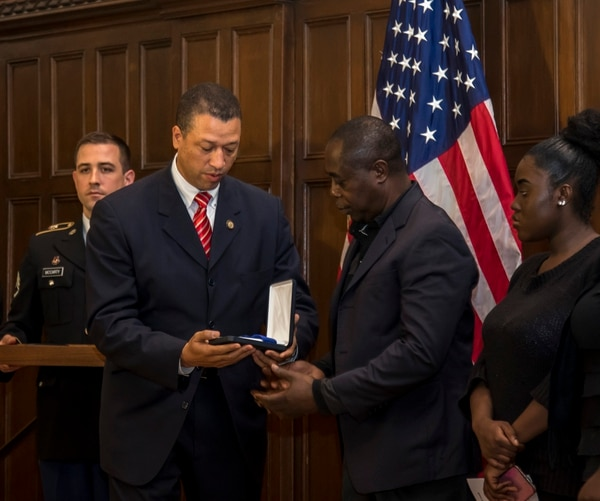 Richard White, New York State Deputy Secretary for Public Safety, presents Kwabena O. Mensah, father of Pfc. Emmanuel Mensah, with the New York State Medal for Valor, the state's highest military award, during a ceremony at Keating Hall, Fordham University. (Staff Sgt. Michael Davis/Army)