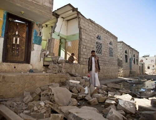 A Yemeni man stands near his house on March 31, 2015, after it was destroyed by Saudi airstrikes. (Hani Mohammed/AP)