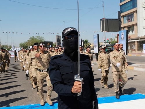 In this May 31, 2019, file photo, Iraqi Popular Mobilization Forces march in Baghdad, Iraq. (Khalid Mohammed/AP)