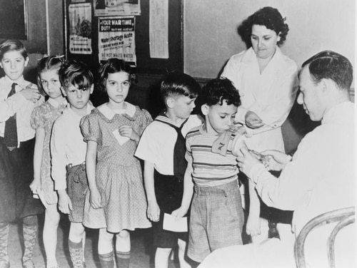School children waiting in line for immunization shots at a child health station in New York City during World War II. (Library of Congress)