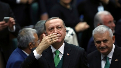 Turkey's president and leader of ruling Justice and Development Party Recep Tayyip Erdogan, left, salutes before he addresses his lawmakers at the parliament in Ankara, Turkey, Tuesday, Jan. 16, 2018. (Burhan Ozbilici/AP)