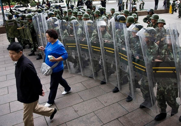 On Sept. 5, 2009, Chinese paramilitary police formed a line to disperse crowds after the unconfirmed report of a needle attack on a boy outside the People's Square in Urumqi, Xinjiang province, China. (Andy Wong/AP)