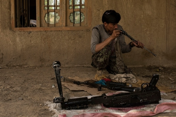 A soldier with the Afghan National Army cleans his weapon at an outpost in Momand Valley on July 16, 2017, in Achin District, Afghanistan. (Andrew Renneisen/Getty Images)