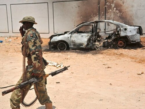 A Somali soldier patrols next to the burnt-out wreckage of a car that was used by suspected al-Shabab fighters in April. (Mohamed Abdiwahab/AFP/Getty Images)