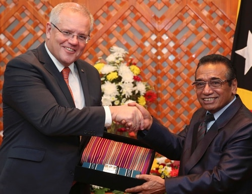 Australian Prime Minister Scott Morrison, left, receives the gift of traditional Timorese woven cloths called 'tais' from East Timorese President Francisco Guterres during their Friday meeting in Dili, East Timor. (Kandhi Barnez/AP)