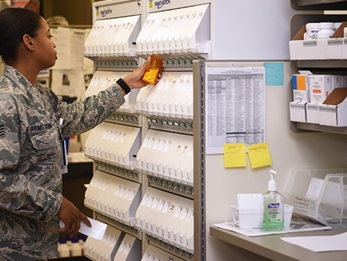 Air Force Staff Sgt. Montea Armstrong fills a prescription at the pharmacy on Goodfellow Air Force Base, Texas, March 23. Officials activated a drive-in pharmacy to minimize personnel in the clinics and medical staff delivered prescriptions to the patients outside the clinic in their cars. (Airman 1st Class Abbey Rieves/Air Force)
