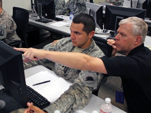 Ken Foster, a computer network analyst with the California Army National Guard Computer Network Defense Team, assists one of his fellow analysts to defend against a simulated virus attack during the 2014 Cyber Shield exercise at the National Guard Professional Education Center in North Little Rock, Ark., on April 30, 2014. (Capt. Kyle Key/U.S. Army National Guard)