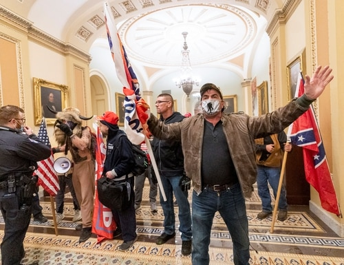 Rioters supporting President Donald Trump's claims of election fraud confront U.S. Capitol Police officers outside the Senate Chamber after breaking into the Capitol building on Jan. 6, 2021. (Manuel Balce Ceneta/AP)