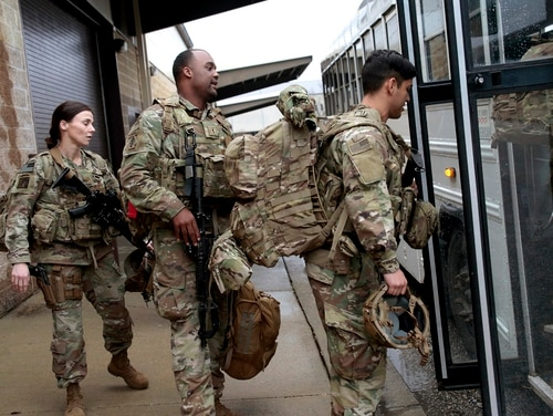 In this Jan. 4, 2020, file photo, U.S. Army soldiers with their gear board an awaiting bus at Fort Bragg, N.C., as troops from the 82nd Airborne are deployed to the Middle East. (Chris Seward/AP)
