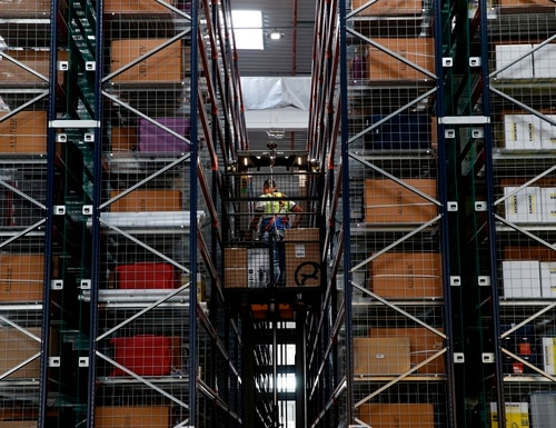 Employees work during a visit by the French president to the Amazon factory in Boves, near Amiens, northern France, on Oct. 3, 2017. (Yoan Valat/AFP via Getty Images)