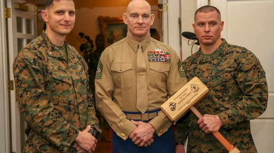 Lt. Col. Jason C. Armas, commanding officer, 1st Reconnaissance Battalion (left), Sgt. Maj. Troy E. Black, sergeant major of the Marine Corps, and Sgt. Maj. James L. Horr, sergeant major, 1st Reconnaissance Battalion, Camp Pendleton, California, pose with the Superior Unit Physical Fitness Award. The new award recognizes the command with the highest combined physical and combat fitness performance around the Marine Corps. (Lance Cpl. Piper A. Ballantine/Marine Corps)