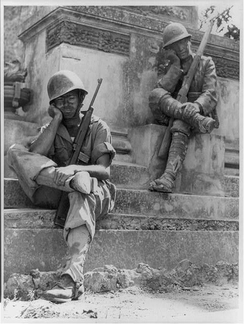 Tired and foot-weary from his march to Brolo, Sicily, during the invasion of Sicily, Sgt. Norwood Dorman, Benson, North Carolina, falls into the pose of the statue in this memorial to the Italian soldier of World War I] , July 1943. (U.S. Army Signal Corps)