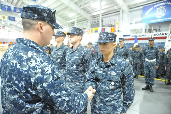 GREAT LAKES, Ill. (August 20, 2015) -- Seaman Recruit Joseph V. Agbingpadua, of Mission Hills, Calif., receives the first Recruit Honor Graduate Ribbon during his Pass-In-Review (PIR) rehearsal in the Midway Ceremonial Drill Hall at Recruit Training Command, Great Lakes, Aug. 20. The Honorable Secretary of the Navy Ray Mabus approved the award to recognize initial accession enlisted personnel who demonstrate superior performance throughout basic military training in the areas of academics, physical readiness, recruit leadership and commitment to the Navy Core Values. Honor Graduates earning the ribbon will be authorized to wear it during the PIR graduation ceremony held on most Friday during the year. No more than 3 percent of graduates from each training group will be designated as Honor Graduates. (U.S. Navy Photo by Susan Krawczyk/RELEASED)