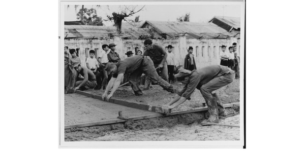Seabees of U.S. Naval Mobile Construction Battalion 11 level the concrete poured for the base of a school at the Quang Tri Combat Base. (National Archives)