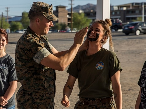 1st. Lt. Curtis Krueger, communications officer, Combat Logistics Battalion 7, demonstrates how to apply camouflage paint on Ashlie Stapp, during the unit's Jane Wayne Day aboard the Marine Corps Air Ground Combat Center, Twentynine Palms, California May 10, 2018. (Lance Cpl. Margaret Gale/Marine Corps)