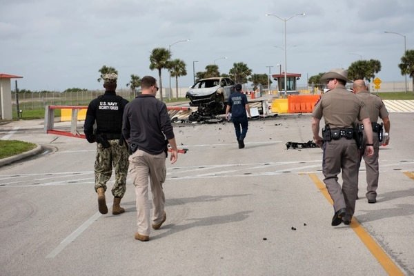 U.S. Navy Security Forces, Naval Criminal Investigative Services, and Texas Department of Public Safety survey the crash scene after a vehicle unlawfully entered the base on Thursday morning. (Anne Owens/Navy)