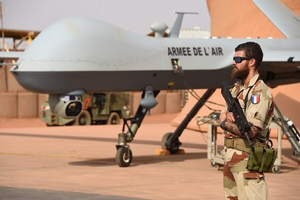 A French soldier involved in the regional anti-insurgent Operation Barkhane stands guard next to a Reaper drone at the French military airbase in Niamey on March 14, 2016. Barkhane, which succeeded Serval in 2014, has at least 3,500 soldiers deployed across five countries -- Burkina Faso, Chad, Mali, Mauritania and Niger -- to combat jihadist jihadist insurgencies. / AFP / PASCAL GUYOT (Photo credit should read PASCAL GUYOT/AFP/Getty Images)