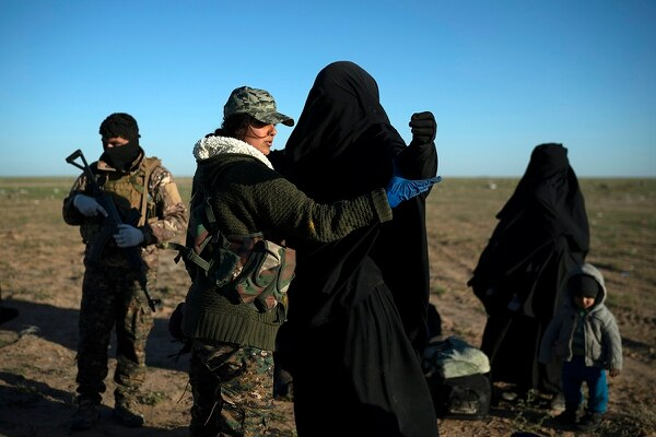 A woman is frisked by an American-backed Syrian Democratic Forces fighter on March 1, 2019, at a screening area after being evacuated out of the last territory held by ISIS militants, in the desert outside Baghouz, Syria. (Felipe Dana/AP)