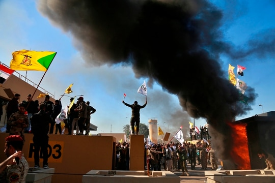In this Dec 31, 2019, file photo, protesters burn property in front of the U.S. embassy compound, in Baghdad, Iraq. (Khalid Mohammed/AP)